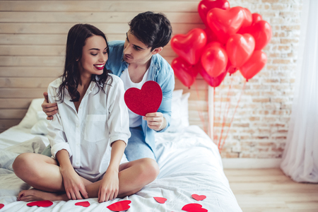 Beautiful young couple in bedroom. Celebrating Saint Valentines Day.