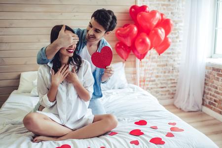 Bella giovane coppia in camera da letto. Festeggiamo San Valentino.