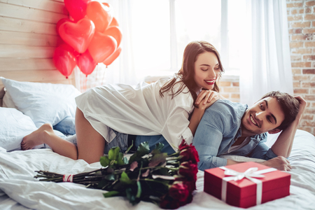Beautiful young couple in bedroom is lying on bed with gift box and red roses nearby. Celebrating Saint Valentines Day.