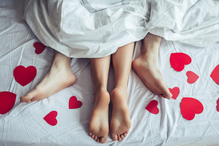 Cropped image of young couple is lying on bed. Close up of male and female feet. Loving couple is lying on bed under blanket covered by small red paper hearts. Saint Valentines Day. Фото со стока
