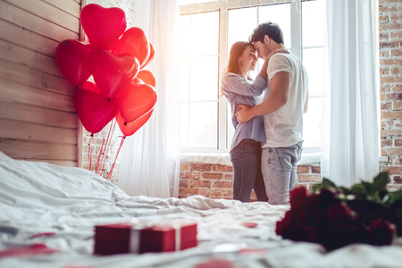 Beautiful young couple at home. Hugging, kissing and enjoying spending time together while celebrating Saint Valentine's Day with red roses on bed and air balloons in shape of heart on the background. 免版税图像 - 93049364