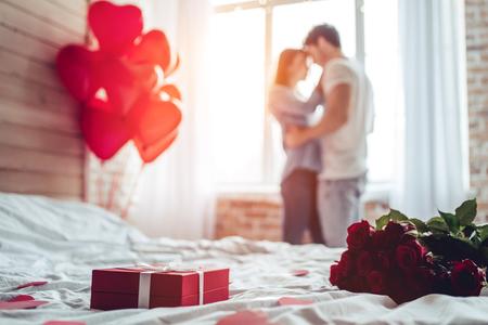 Piękna młoda para w domu. Przytulanie, całowanie i wspólne spędzanie czasu podczas świętowania Walentynek z czerwonymi różami na łóżku i balonami w kształcie serca na tle. Zdjęcie Seryjne