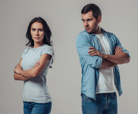 美しいロマンチックなカップルは、灰色の背景に孤立しました。けんかしている間、お互いに離れて立っている。