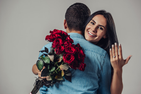 Beautiful romantic couple in love isolated on grey background. Attractive young woman with ring on hand is holding red roses while hugging her handsome man. Just engaged. Happy Saint Valentine's Day!
