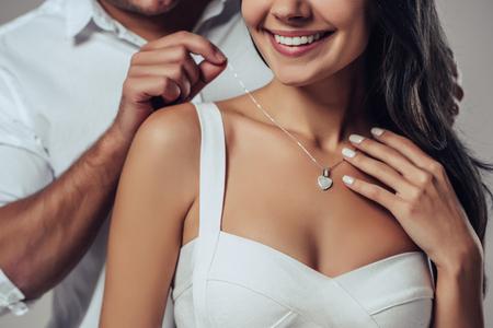 Schöne romantische Paare in der Liebe lokalisiert auf grauem Hintergrund. Gut aussehender Mann trägt Halskette auf seiner attraktiven jungen Frau. Fröhlichen Valentinstag!