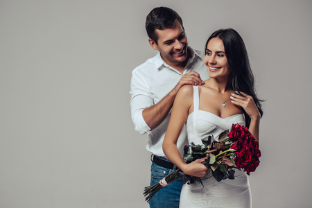 Beautiful romantic couple in love isolated on grey background. Handsome man is wearing necklace on his attractive young woman. Happy Saint Valentine's Day! Stock Photo