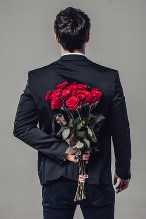 Handsome yound man in suit is standing with red roses behind the back on grey background.