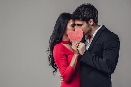 Beautiful romantic couple isolated on grey background. Attractive young woman in red dress and handsome man in suit are kissing and hiding behind the red heart. Happy Saint Valentines Day!