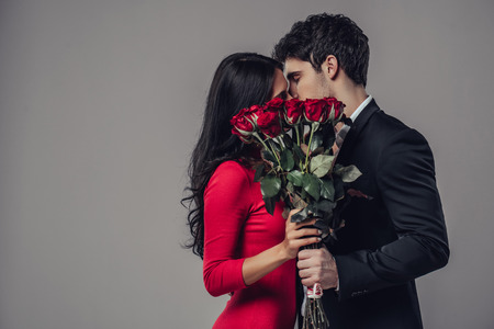 Beautiful romantic couple isolated on grey background. Attractive young woman in dress holding red roses and handsome man in suit are kissing. Happy Saint Valentines Day!