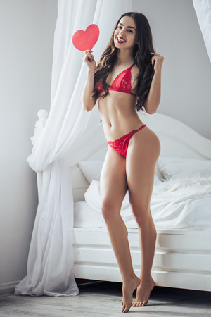 Young sexy woman is standing near bed in red lingerie with red heart in hand and smiling. Happy Saint Valentines Day!