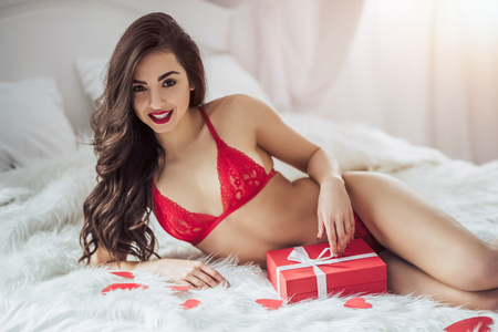 Young sexy woman is lying on bed in red lingerie with red heart in hand and smiling. Happy Saint Valentines Day!
