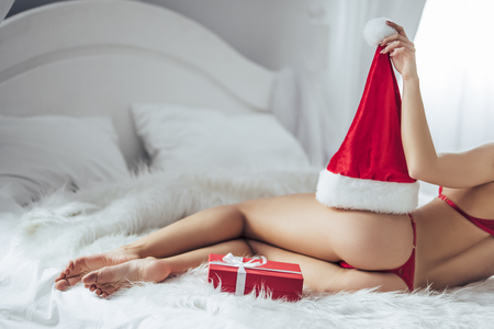 Cropped image of sexy young woman is lying on bed in red lingerie with Santa Claus hat and gift box nearby. Merry Christmas and Happy New Year!