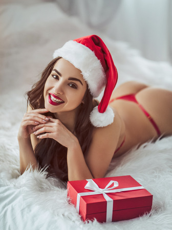 Sexy young woman is lying on bed in red lingerie with Santa Claus hat and gift box nearby. Merry Christmas and Happy New Year! Stock Photo