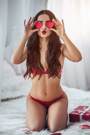 Young sexy woman is sitting on bed in red lingerie with red hearts in hands and giving air kisses. Happy Saint Valentines Day!