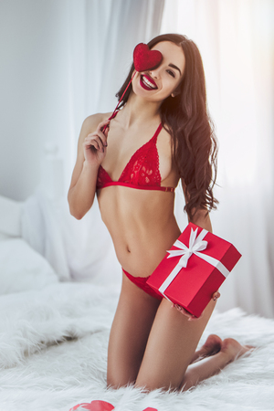 Young sexy woman is sitting on bed in red lingerie with red heart in hand and gift box nearby. Happy Saint Valentines Day!