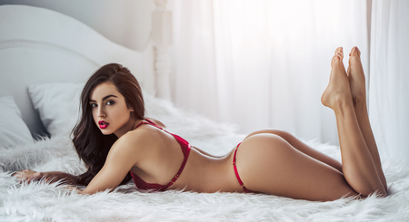Young sexy woman is lying on white bed in red lingerie. Stock Photo