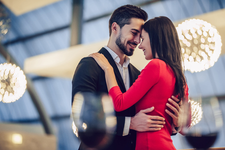 Lindo casal apaixonado está gastando tempo juntos no restaurante moderno. Mulher jovem e atraente no vestido e homem bonito terno estão tendo um jantar romântico. Celebrando o Dia dos Namorados. Foto de archivo - 93595715