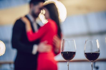 美しい愛情のあるカップルは、モダンなレストランで一緒に時間を過ごしています。ドレスとスーツのハンサムな男性の魅力的な若い女性は、ロマ 写真素材