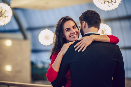Beautiful loving couple is spending time together in modern restaurant. Attractive young woman in dress and handsome man in suit are having romantic dinner. Celebrating Saint Valentines Day. Banco de Imagens