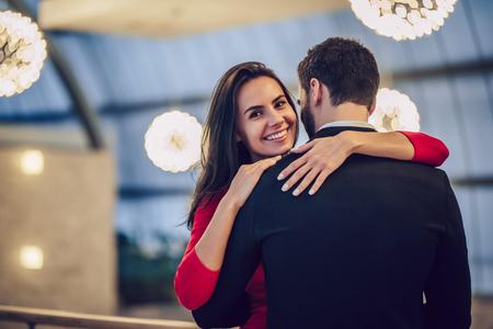 Lindo casal apaixonado está gastando tempo juntos no restaurante moderno. Mulher jovem e atraente no vestido e homem bonito terno estão tendo um jantar romântico. Celebrando o Dia dos Namorados. Foto de archivo