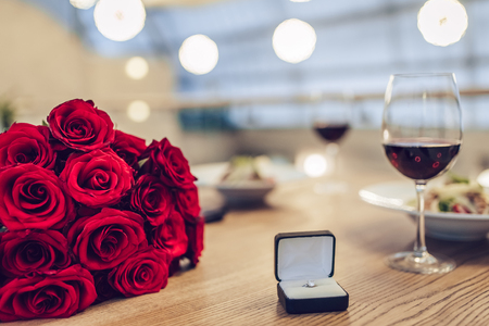 Romantic dinner settings. Two glasses of wine, dishes, bouquet of red roses and engagement ring are on table. Stock Photo