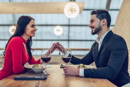 Lindo casal apaixonado está gastando tempo juntos no restaurante moderno. Mulher jovem e atraente no vestido e homem bonito terno estão tendo um jantar romântico. Celebrando o Dia dos Namorados.