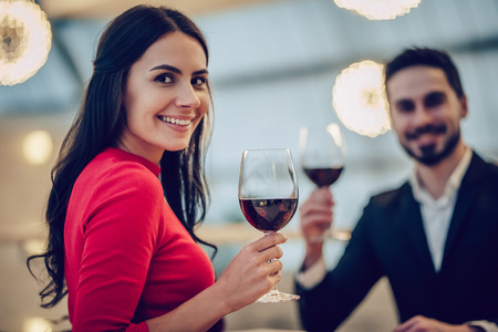 Beautiful loving couple is spending time together in modern restaurant. Attractive young woman in dress and handsome man in suit are having romantic dinner. Celebrating Saint Valentines Day. Stock Photo