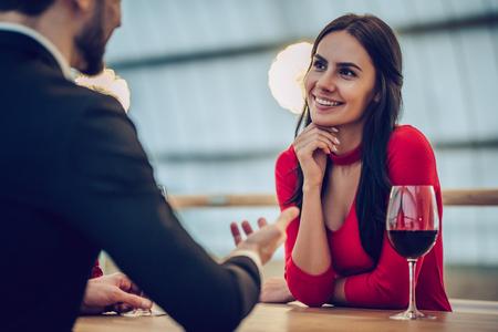 Beau couple d'amoureux passe du temps ensemble dans un restaurant moderne. Belle jeune femme en robe et bel homme en costume ont un dîner romantique. Célébrer la Saint Valentin. Banque d'images - 93595792