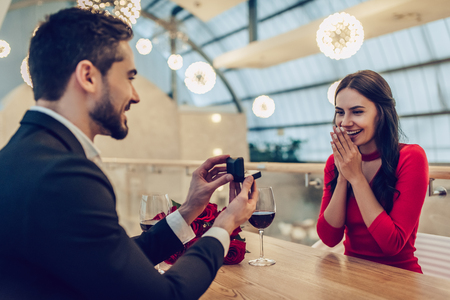 Beautiful loving couple is spending time together in modern restaurant. Attractive young woman in dress and handsome man in suit are having romantic dinner. Celebrating Saint Valentines Day. Stok Fotoğraf