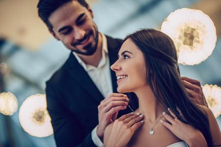 Schönes Liebespaar verbringt Zeit zusammen im modernen Restaurant. Attraktive junge Frau im Kleid und gutaussehender Mann in der Klage essen romantisches zu Abend. Valentinstag feiern. Standard-Bild