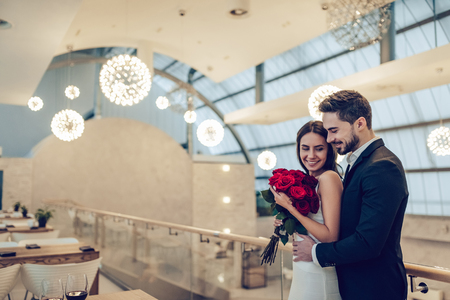 Beautiful loving couple is spending time together in modern restaurant. Attractive young woman in dress and handsome man in suit are having romantic dinner. Celebrating Saint Valentine's Day.