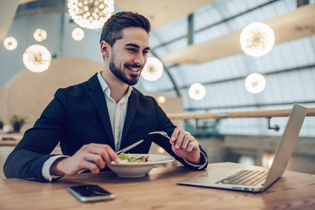 Handsome businessman is sitting in modern restaurant and working with laptop Stock Photo