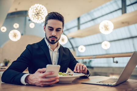 Handsome businessman is sitting in modern restaurant with smart phone and laptop. Stock Photo