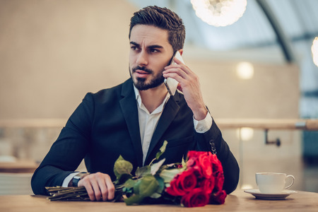 Handsome businessman is sitting in modern restaurant with bouquet of red roses and talking on mobile phone while waiting for his beloved. Stock Photo