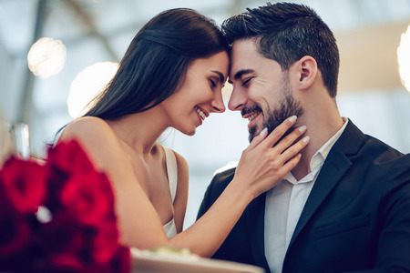 Schönes Liebespaar verbringt Zeit zusammen im modernen Restaurant. Attraktive junge Frau im Kleid und gutaussehender Mann in der Klage essen romantisches zu Abend. Valentinstag feiern.