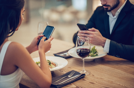 Cropped image of loving couple is spending time together in modern restaurant. Attractive young woman in dress and handsome man in suit are having romantic dinner. Celebrating Saint Valentines Day.