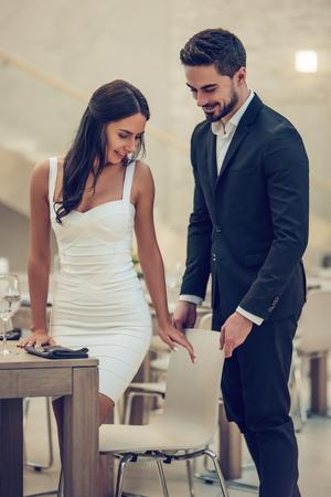 美しい愛情のあるカップルは、モダンなレストランで一緒に時間を過ごしています。ドレスとスーツのハンサムな男性の魅力的な若い女性は、ロマンチックなディナーを持っています。聖バレンタインデーを祝う。 写真素材 - 93595828