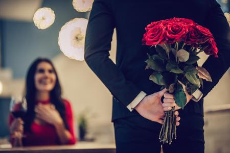 Beau couple d'amoureux passe du temps ensemble dans un restaurant moderne. Belle jeune femme en robe et bel homme en costume ont un dîner romantique. Célébrer la Saint Valentin. Banque d'images - 93594523