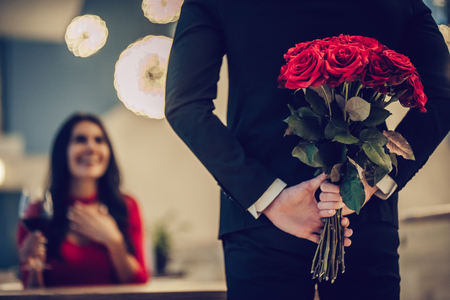 Beautiful loving couple is spending time together in modern restaurant. Attractive young woman in dress and handsome man in suit are having romantic dinner. Celebrating Saint Valentines Day. Фото со стока