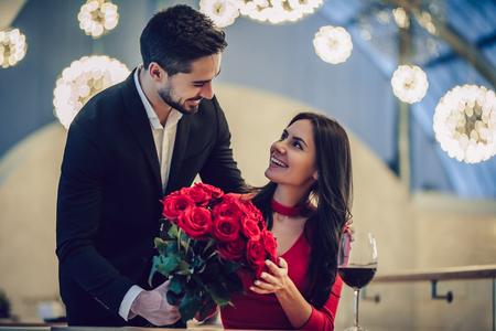 Beau couple d'amoureux passe du temps ensemble dans un restaurant moderne. Belle jeune femme en robe et bel homme en costume ont un dîner romantique. Célébrer la Saint Valentin. Banque d'images - 93594526