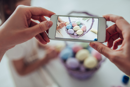Cropped image of attractive young woman with little cute girl are preparing for Easter celebration. Mom and daughter are painting eggs and making photo on a smart phone. Stock Photo