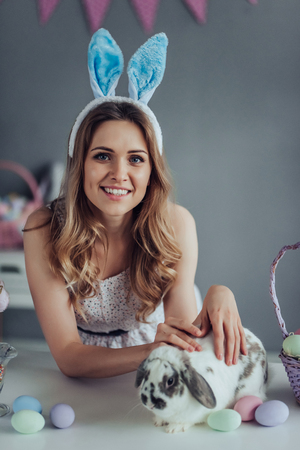 Attrective young woman wearing bunny ears is preparing for Easter celebration while having fun with Easter bunny at home. Stock Photo