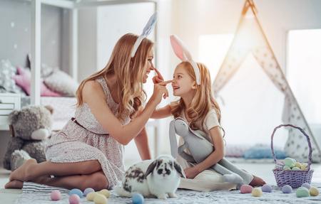 Belle jeune femme avec une petite fille mignonne se préparent pour la célébration de Pâques. Maman et sa fille portant des oreilles de lapin s'amusent avec un lapin de Pâques assis sur le sol à la maison. Banque d'images - 94063439