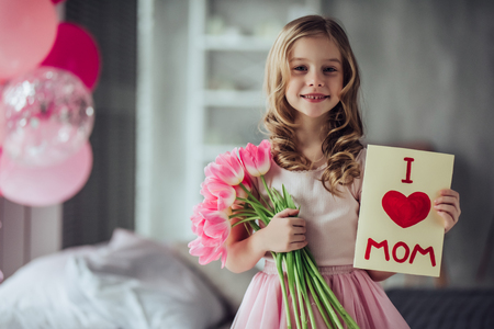 I love my mom! Little cute girl with bouquet of pink tulips at home. Happy Mother's Day! Standard-Bild