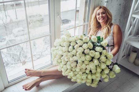 何百もの白いバラの花束を持つ魅力的な若い女性は、自宅で時間を過ごしています。