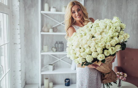 Attractive young woman with bouquet of hundreds of white roses is spending time at home.