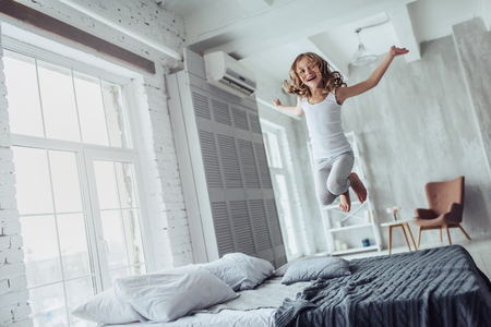 Little cute girl is jumping on bed at home in a light bedroom.