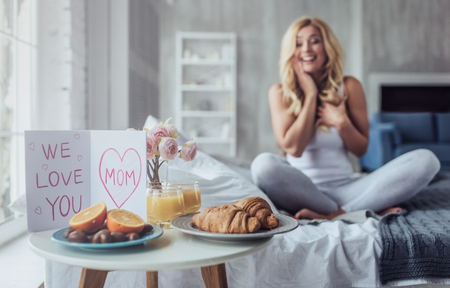 We love you, mom! Attractive young woman is sitting on bed at home. Breakfast in bed on Mothers Day with a children postcard.