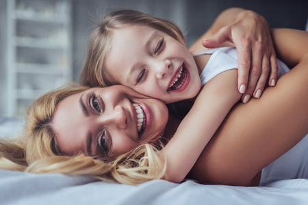 Attractive young woman with little cute girl are spending time together at home. Lying on bed, hugging and having fun. Happy family concept. Mothers day. 스톡 콘텐츠