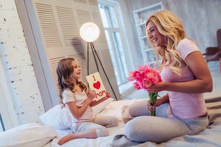 I love you, mom Attractive young woman with little cute girl are sitting on bed and spending time together at home. Mom is receiving presents from daughter on Mothers Day. Happy family concept. 스톡 콘텐츠